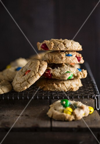 Cookies with colourful chocolate beans on a wire rack
