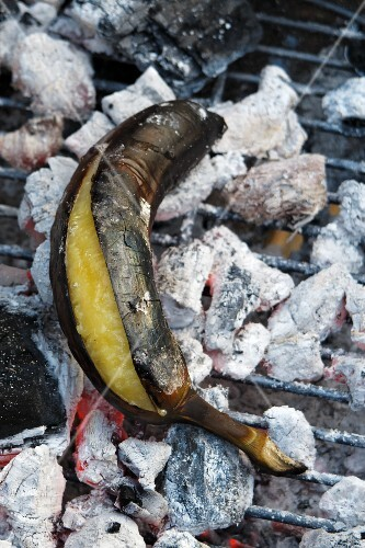 A grilled plantain on hot coals