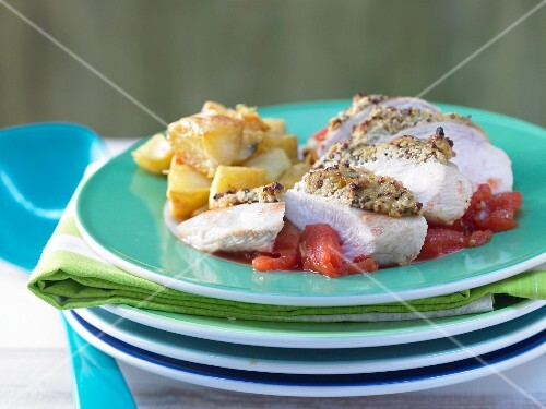 Chicken breast with an olive crust on tomato sauce