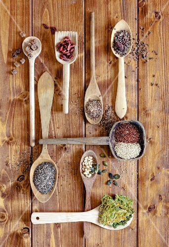 Dried superfoods on wooden spoons (seen from above)