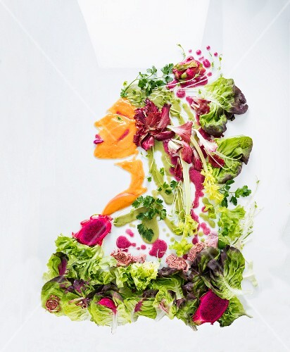 A portrait of a woman made from lettuce, vegetables and fruit on a white surface