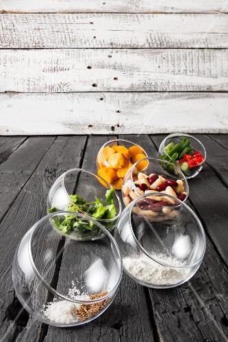 Ingredients for gluten-free veggie burgers in glass bowls