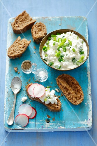 A slice wholemeal roll topped with cottage cheese and radishes