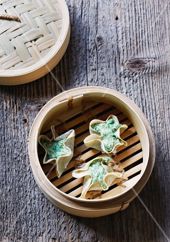 Dim sum with tofu and spinach in a bamboo steamer