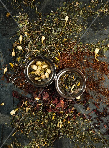 Various types of herb tea scattered on a wooden surface