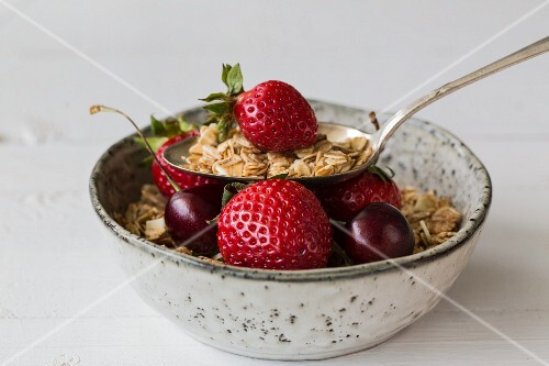 A bowl of muesli with strawberries and cherries