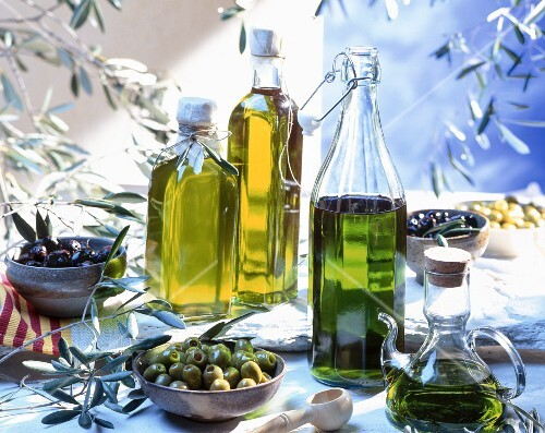 An arrangement of various olives and olive oils