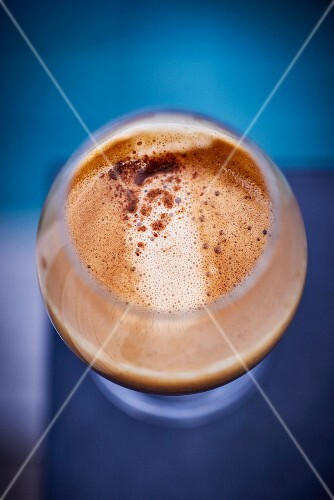 A view from above of a stemmed glass with coffee and coffee foam