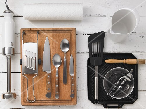 Kitchen utensils: a hand blender, a slicer, cutlery, a grillg pan, a spatula and a mixing bowl