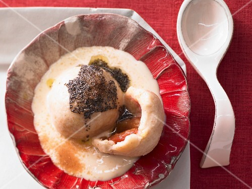 A plum dumpling with poppy seeds and orange sauce