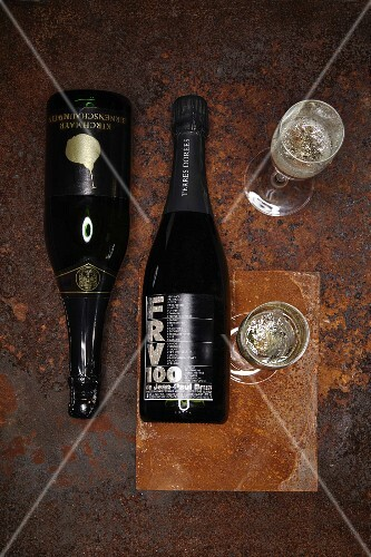 Sparkling pear wine and Beaujolais sparkling wine in bottles and glasses