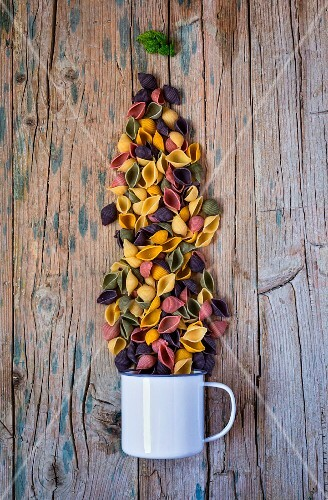 Colourful pasta with an enamel mug on a wooden table