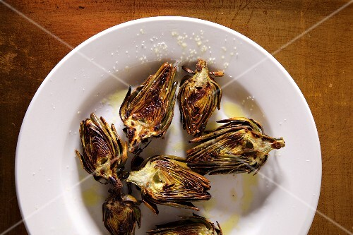 Grilled artichokes on a plate with salt