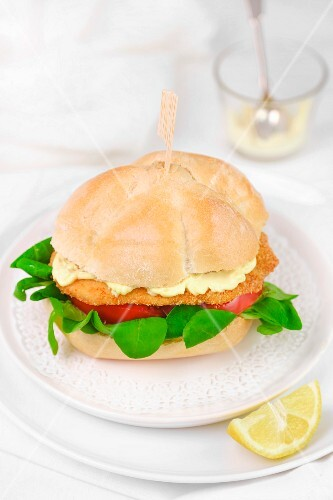 A breaded escalope in a roll with tomato and mayonnaise