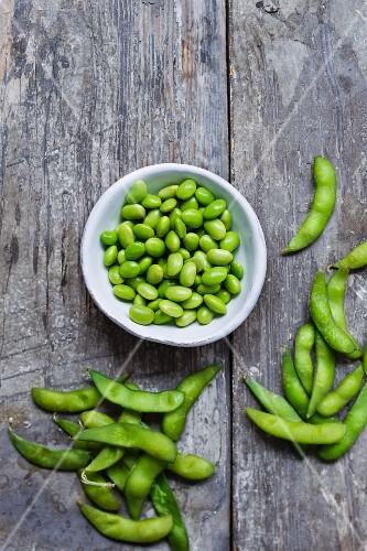 Edamame beans in a bowl and on a wooden surface