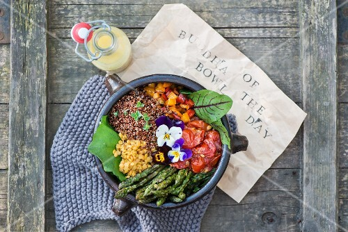 A Buddha Bowl with lentils, asparagus, tomatoes, peppers, lettuce and pansies