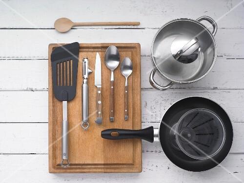 Various kitchen utensils: a pot, a pan, cutlery, a peeler and a spatula