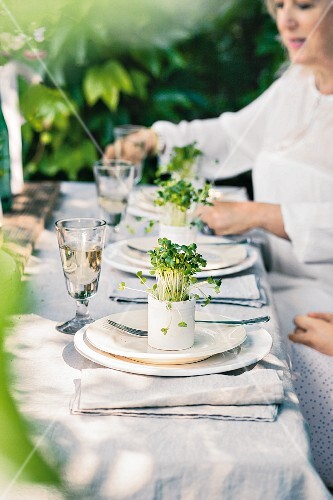 A festively set outdoor table decorated with pots of cress