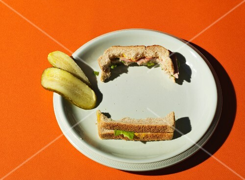 A half-eaten New York Deli sandwich and sliced gherkin on a white plate