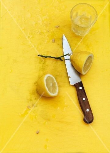 A Sicilian lemon sliced in half against a yellow background