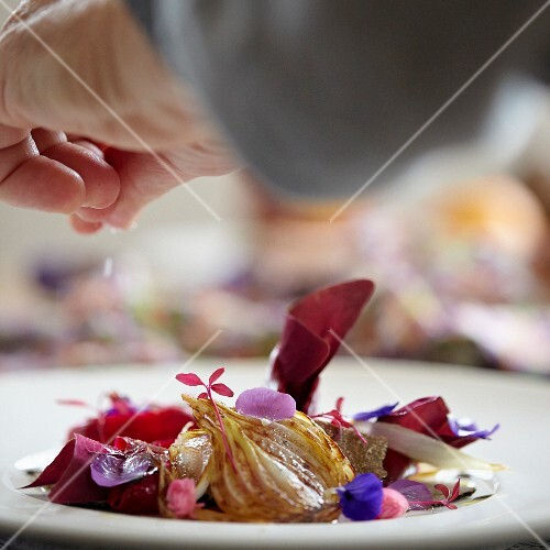 Sprinkling salt on beetroot salad with onion, truffle and edible flowers