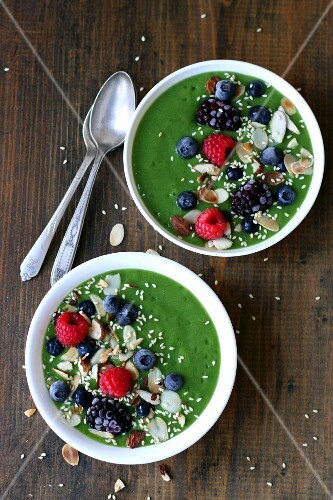 Green smoothie bowls with berries, nuts and seeds