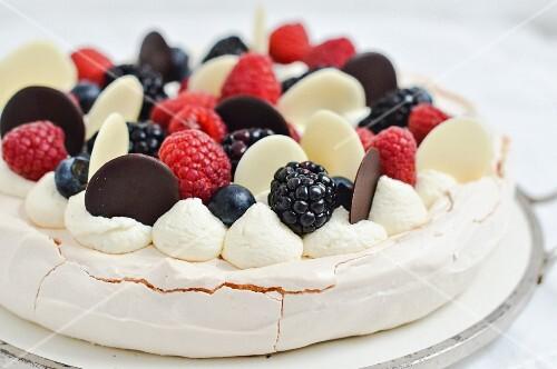 Pavlolva with whipped cream, raspberries and blueberries