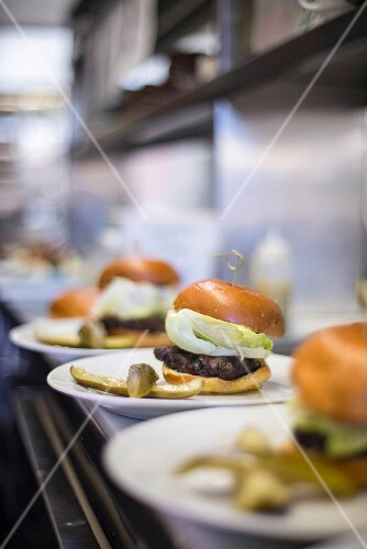 A row of burgers lined up ready to serve in a restaurant
