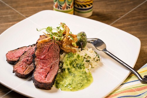 A flank steak with rice and vegetables
