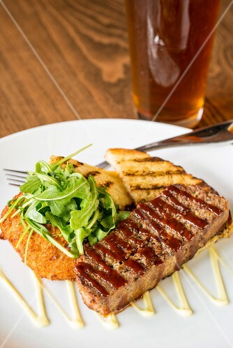 Grilled bread with meatloaf and rocket on a plate in front of the glass of beer