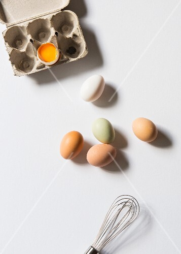 Fresh chicken eggs next to an egg box with a cracked open egg