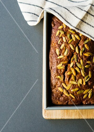 Pumpkin and walnut bread in a baking tin (seen from above)