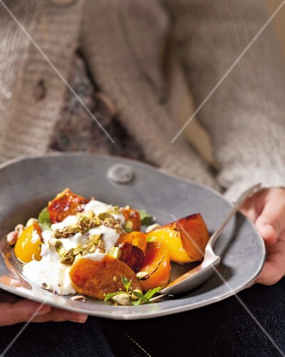Grilled Sharon fruit with yoghurt, honey and pistachios