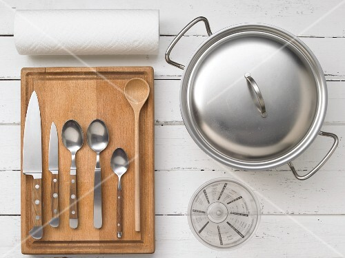 Assorted kitchen utensils: cutlery, a measuring cup, a saucepan and kitchen roll