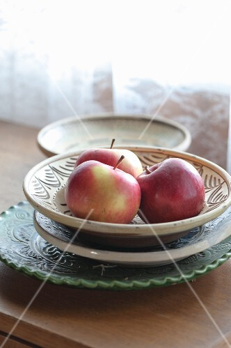 Three red apples in a bowl on the windowsill