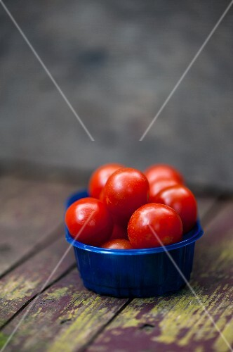 Cocktail tomatoes in a blue plastic bowl