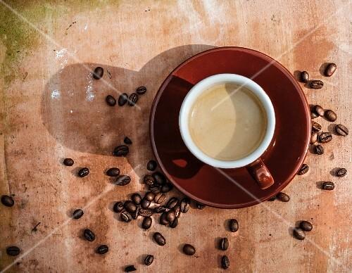 Cafe Crema in Tasse umgeben von Kaffeebohnen (Aufsicht)