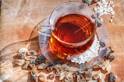 Tea in a glass cup surrounded by rock sugar