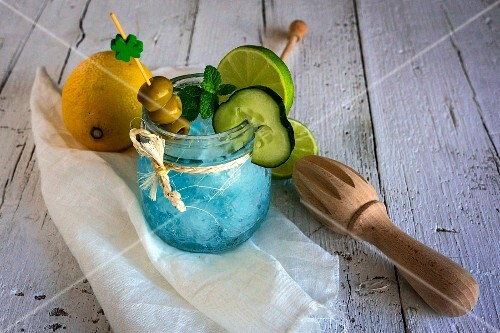 A gin and tonic garnished with olives, cucumber and lime served in a preserving jar