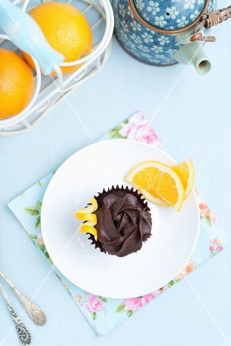 An orange & chocolate cupcake with chocolate frosting (see from above)
