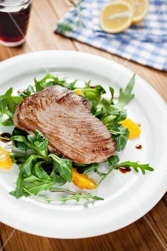 Tuna fish fillet on a rocket salad with orange fillets