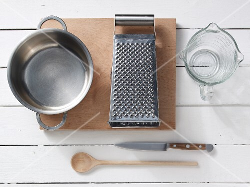 Kitchen utensils: a saucepan, a grater, a measuring cup, a wooden spoon and a knife