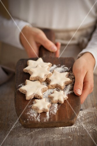 A woman holding cinnamon stars on a wooden board