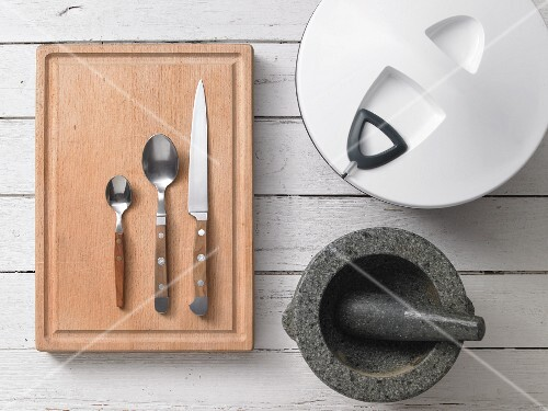 Assorted kitchen utensils: cutlery, a salad spinner and a pestle and mortar