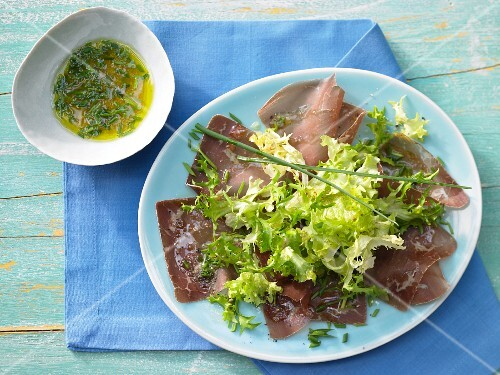 Frisee lettuce on a bed of ham carpaccio