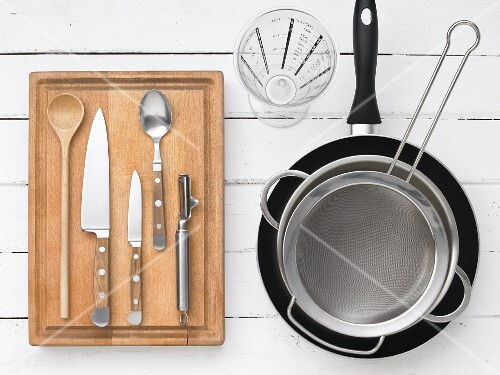Kitchen utensils for preparing spiral pasta with tomato, leek and nuts