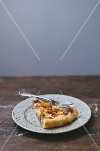 A slice of tomato quiche on a plate