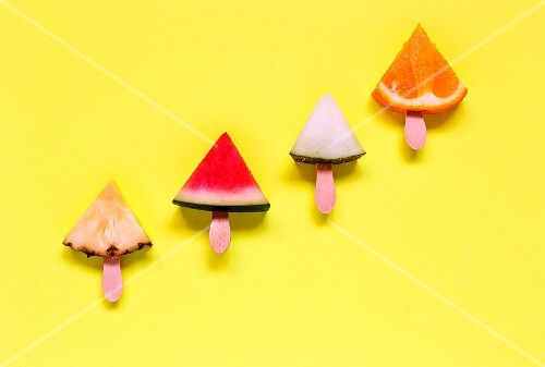 Various sliced fruits on sticks on a yellow surface