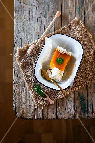 A slice of toasted egg yolk cake with cream and mint