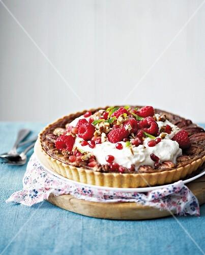 Pecan pie with cream, raspberries and pomegranate seeds